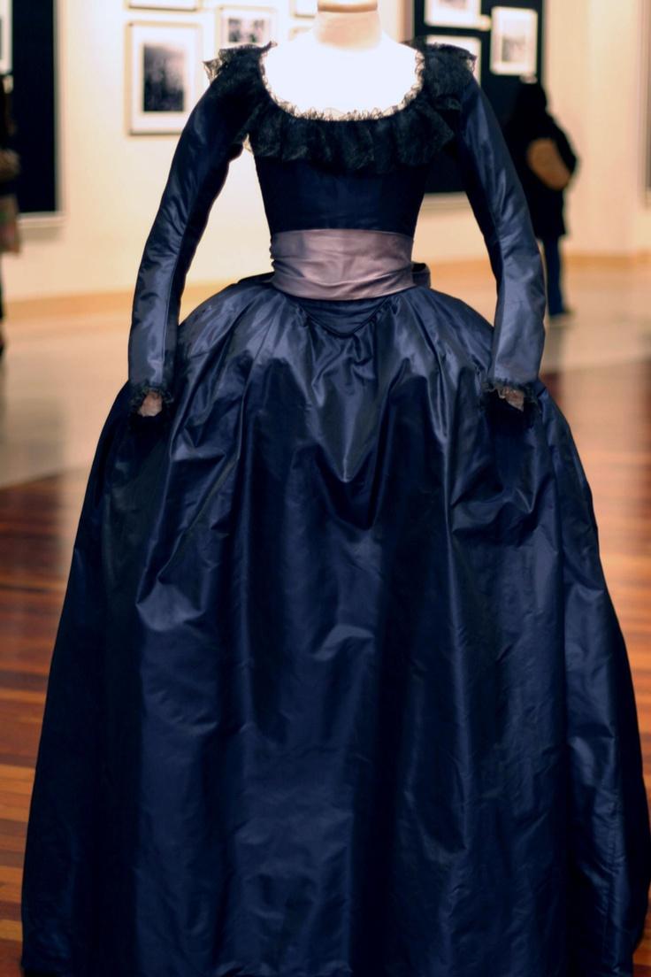 Abito in seta lucida blu scuro dotato di scollo ovale decorato in tulle e fascia larga di seta in vita color rosa/violetto. Costo £250