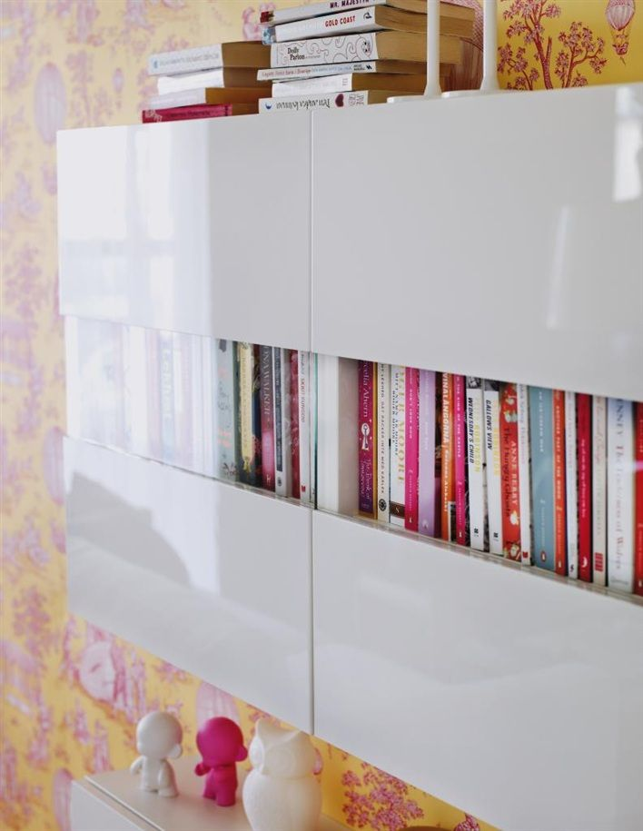 Ikea Besta Shelf Unit With Doors, Wall Cabinets In High Gloss White Finish.  Book Storage In A Small Space. Wallpaper Is A Yellow, Pink And White  Pattern.