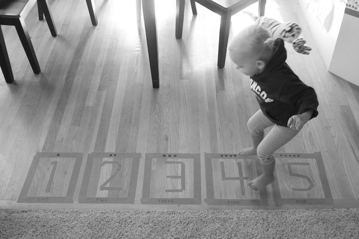 I think this is our favorite learning activity that we've done thus far. I used masking tape to make the numbers one through five on our kitchen floor (planning on making six through ten next week)...