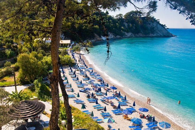 Samos, Greece, sunbeds  with blue umbrellas lined up on a beach.