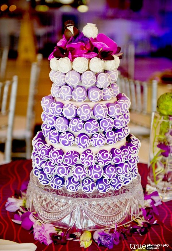 """Stunning """"cake ball cake"""" - this unique wedding cake was created by Cake Ball Love with an """"ombre effect"""" of purple tones. The cake poppers around the edging are edible: crafted from scratch, individually rolled, and hand dipped in chocolate. Looks delicious!"""
