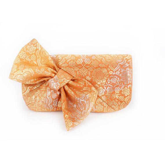 Uno de una bolsa de embrague tipo arco hasta ciclos de tela de kimono de seda del telar jacquar japonés vintage obi. Inspirado en la esencia de la hoja de kimono obi, este embrague arco una oda al arte del arco de la obi en el desgaste de kimono tradicional. MATERIALES Tela base: obi seda jacquard japonesa vintage Patrón: Damasco en naranja y oro Totalmente forrado con bolsillo interno, cierre con monedero broche resorte Viene con caja de regalo y bolsa de polvo. Este embrague es de un…