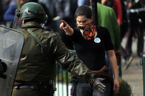 Santiago de Chile - 2011: Durante las manifestaciones estudiantiles contra el gobierno (mayo-noviembre 2011) una joven encara -sin armas ni protección- a un policía antidisturbios. Es la actitud de jóvenes nacidos y crecidos en democracia, defensores de sus derechos y sin miedos irracional ante la autoridad.