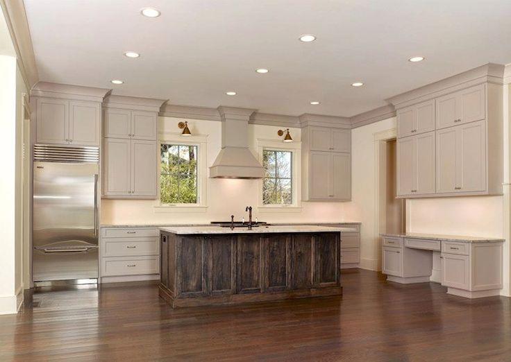 Amazing kitchen featuring taupe kitchen cabinets with taupe crown molding and granite countertops. Rustic dark stained kitchen island and sink with oil-rubbed bronze faucet set