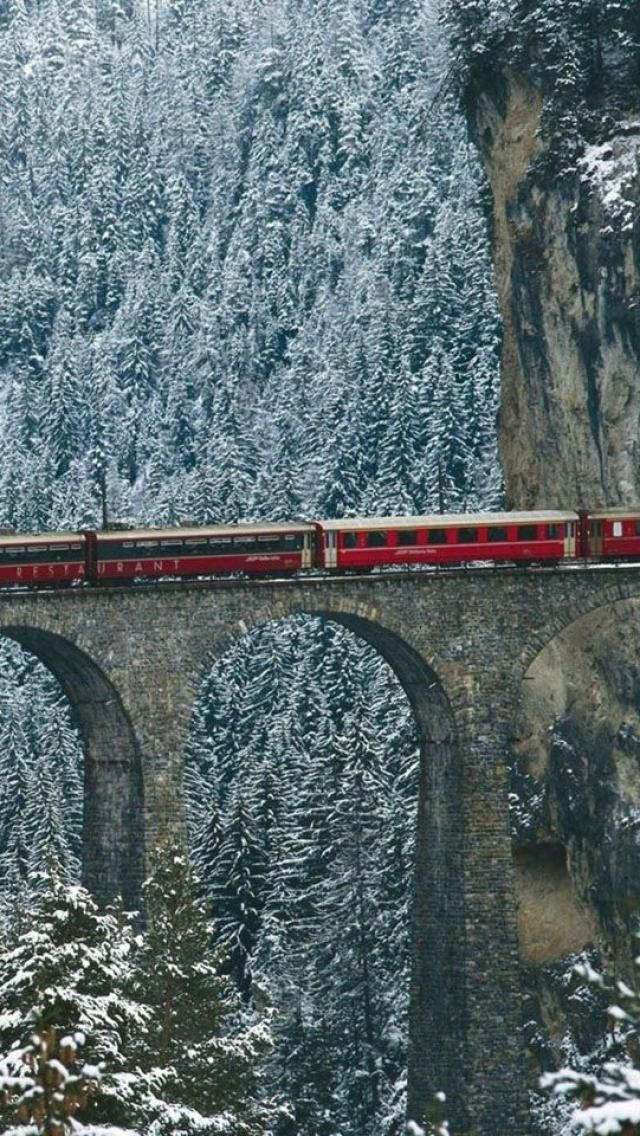 Train passing through Engadine or Engadin Valley in the Swiss Alps, Switzerland.