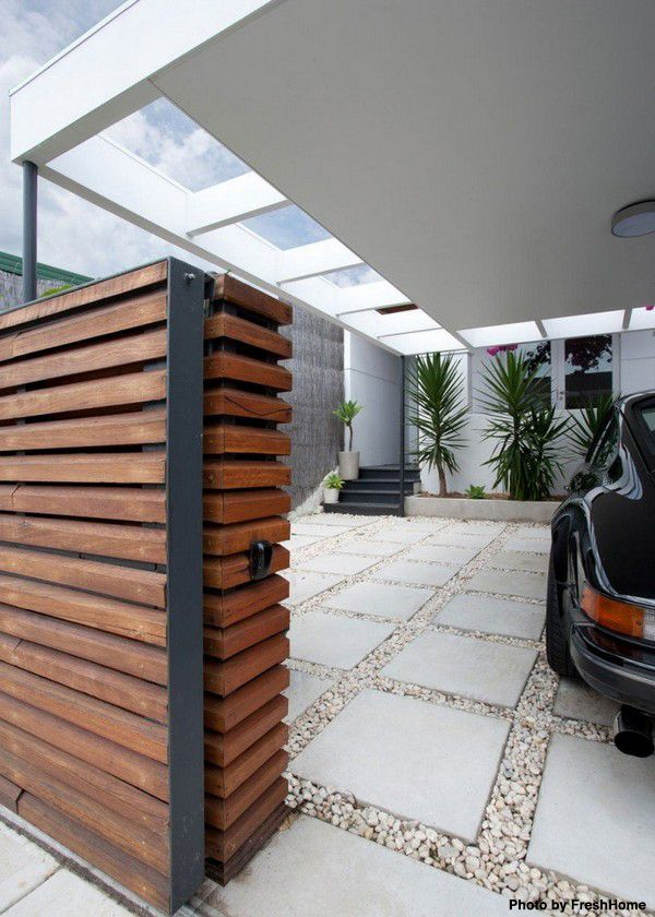 Outdoor, covered garage with with a pebble and paver driveway and a wood garage door. Click on the pin to see what's the average cost of a garage remodel.