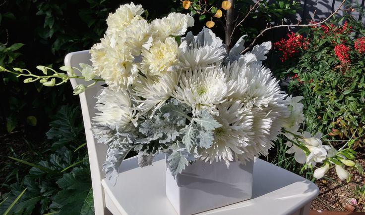 ASYMMETRICAL arrangement featuring dahlias, carnations, eucalyptus, silver suede and freesias.