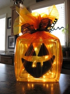 """Square glass votive — from Hobby Lobby or Michael's — filled with string lights (battery operated *or* drill a 1/2"""" hole in the bottom and run an electric set of lights through the hole) - vinyl cut-outs for the face — and wrapped in orange tulle and topped off with a black bow and black pipe cleaners, corkscrewed. CUTE! :)"""