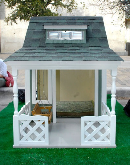 A couple of the entries in:  BARKITECTURE 2012  This quaint canine farmhouse by Henley Homes is equipped with a front porch, swing, dormer window and white picket fence. By Kara Mosher  The rest of the houses are on my Cabins/Treehouses board.