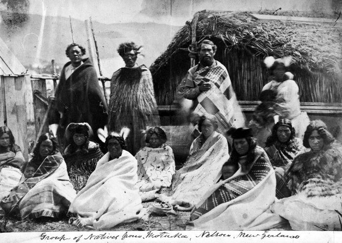 Group from Motueka, [ca 1860s] Group from Motueka outside a whare, circa 1860s. Many are wearing kakahu (traditional Maori cloaks). Unknown photographer.