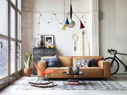 Modern industrial vibes   huge floor to ceiling windows   rounded leather sofa   modern industrial style light pendants   white washed stone walls   Grey cushions pulls the look together - get yours at Bemz