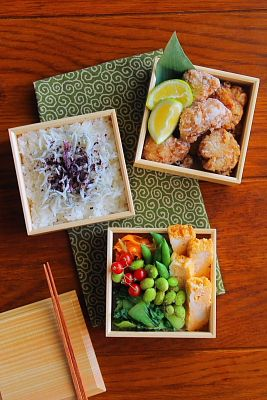 Rice with fish and other seasonings, karaage with lemon or lime wedges, edamame (shelled), what looks like some spinach below that, and I am unsure but maybe agetofu next to that.