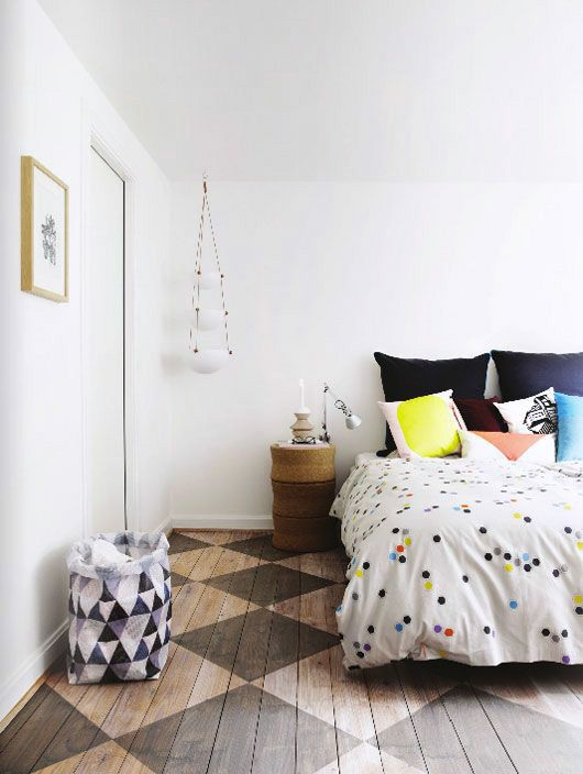 Large bedroom with a dotted beeding, a painted wood flooring in harlequin pattern and colorful pillows.