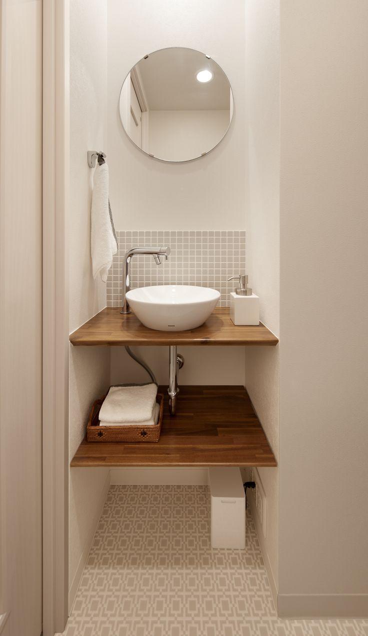 トイレ内の手洗いコーナー。手洗い付き便器ではお子さんの手が手洗いまで届きにくく、水はねの原因になっていました。そこでトイレを少し広げて手洗いスペースを設けました。カウンターは耐水塗装仕上げ。カウンター下はシンプルなオープン収納とし、丸い鏡とベッセル式(置き型)の手洗器でやわらかな印象にまとめました。床は淡いグレーの凹凸のあるCFシート張りとし、同じくグレーのモザイクタイルを水はねしやすい手洗器の前にあしらい、アクセントとしています。このわずかな壁の凹みによって機能的で広がりのあるトイレ空間となりました。 便器背面の吊戸棚は以前のものを再利用。手洗いカウンター上部には、手元が見やすいようにダウンライトを新設。メインのダウンライトと同時にON/OFFできます。洗面室は別にありますが、お子様はこの手洗いコーナーがお気に入り。お家に帰るとここで手を洗うのが日課になりました。