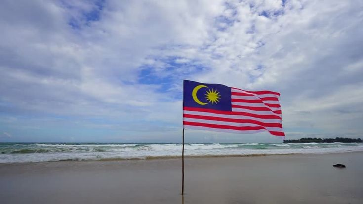Patriotic image of Malaysia's national flag. with its red and white horizontal stripes. flapping in a steady breeze against a sunny. blue sky. beach