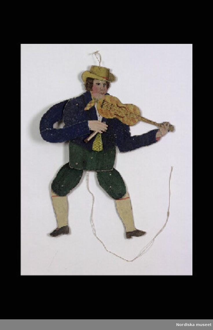 Inventering Sesam 1996-1999:  H 27,5 cm  Sprattelgubbe av handkolorerat papper på kartong föreställande en spelman med brun pagefrisyr klädd i gröna knäbyxor, vita knästrumpor, bruna skor, blå jacka, gul hög hatt, spelande fiol. Halva stråken har gått av. Om man drar i snöret rör sig armar och ben.  Helena Carlsson 1996