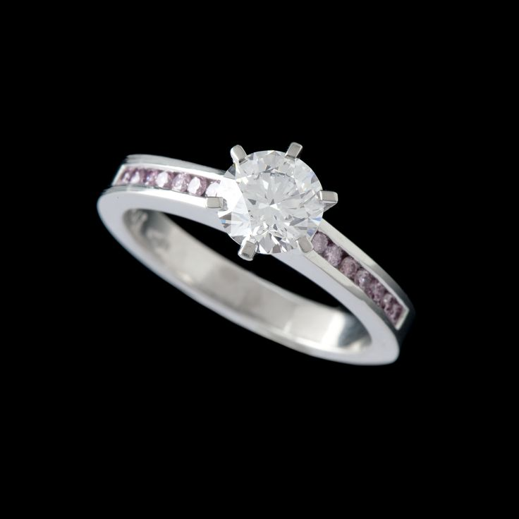 Platinum solitaire diamond ring featuring natural pink diamonds set along the band. Who doesn't love pink diamonds.