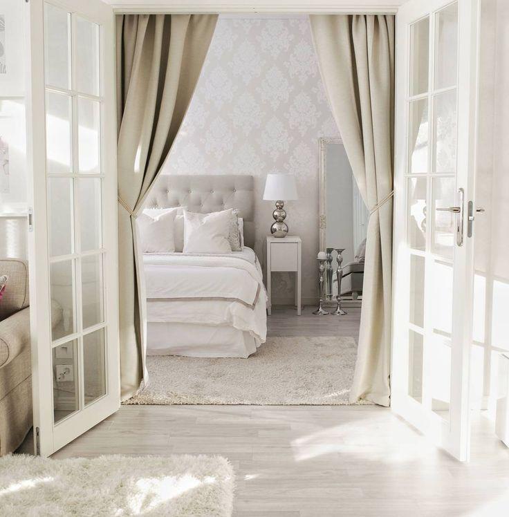 Makuuhuoneeseen vievät pariovet, valoisa vaaleus ja muhkeat verhot loihtivat ylellistä tunnelmaa sisustukseen.