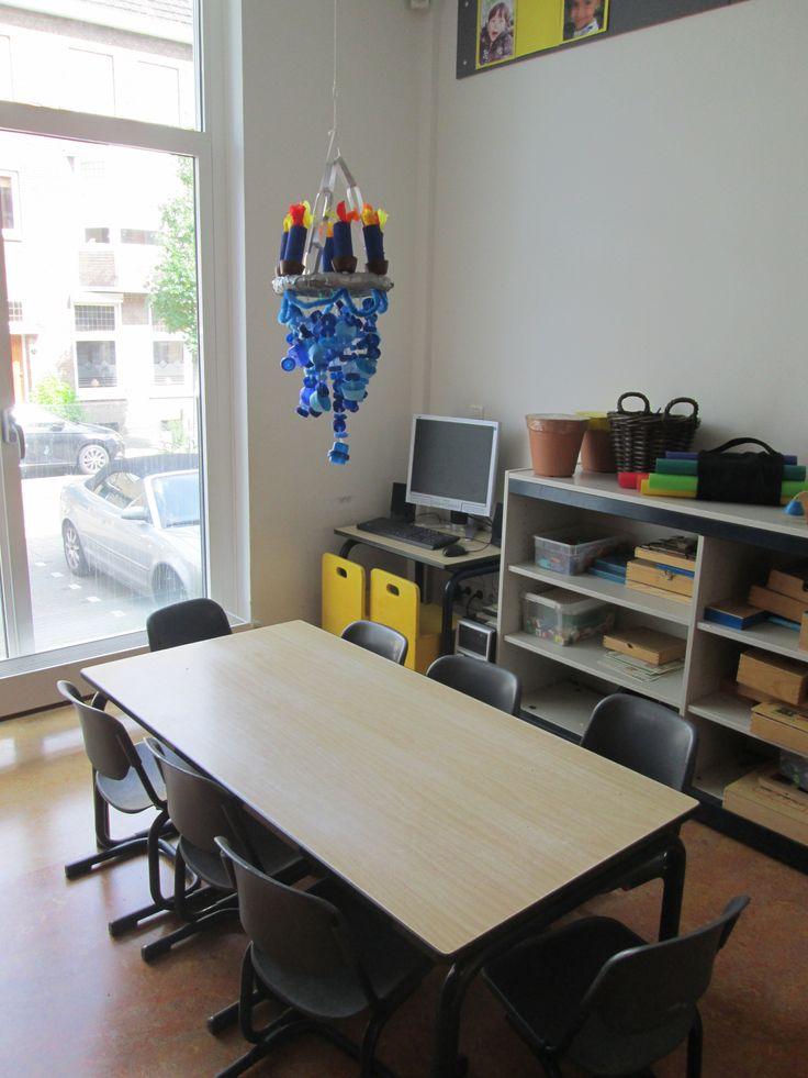 In de klas hebben we een blauwe, gele en groene tafel om aan te werken. Met gekleurde kroonluchters erboven weten de kinderen welke tafel waar is. Nutsschool Maastricht.