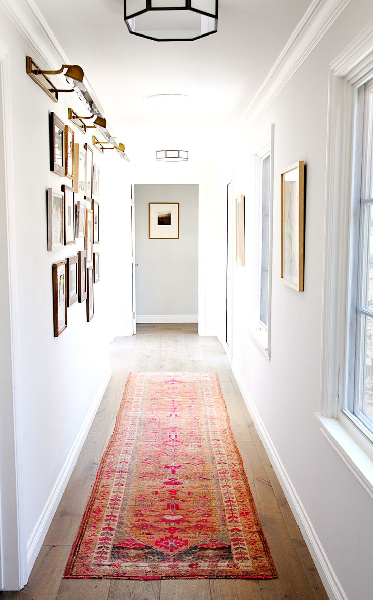 Hallway with white walls, framed artwork, wood floors, and bright patterned rug