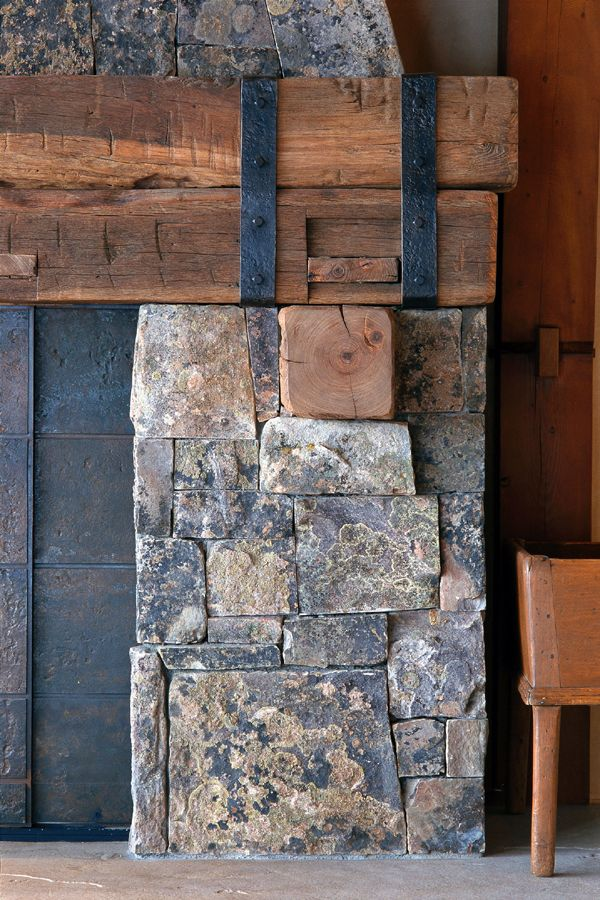 Stone fireplace with lichen coloration and timber beams with wrought iron straps