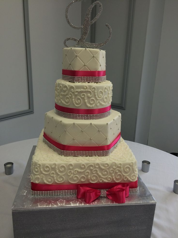 four tier wedding cake with square  hexagon and round tiers  hot pink ribbon and diamond trim