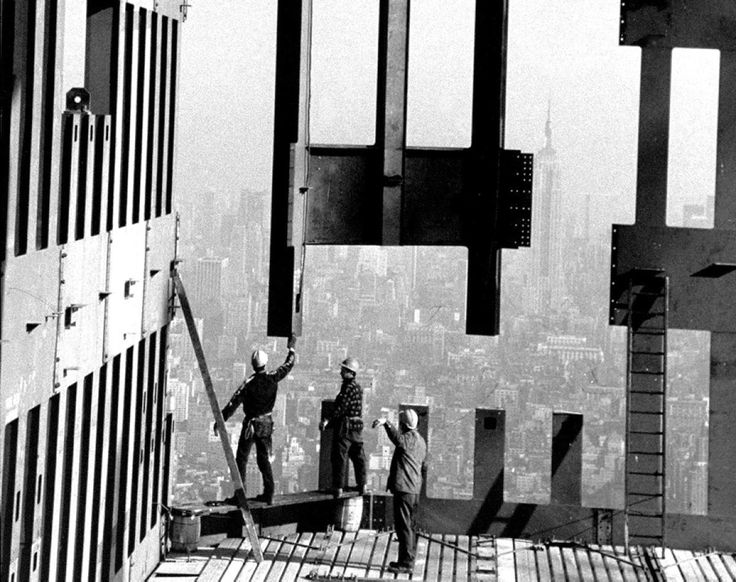 Construction workers put the finishing touches on the top floors of the Twin Towers during the final stages of construction.