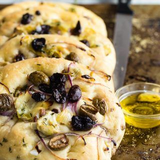 This homemade Focaccia Bread is topped with black and green olives, red onion and artichokes. Use the best olive oil you can get and sprinkle with sea salt for a result that will equal any true Italian bakery.