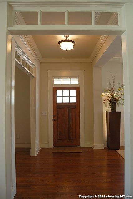 Transom over front door and living entrance to add light to hallway instead of replacing front doors.