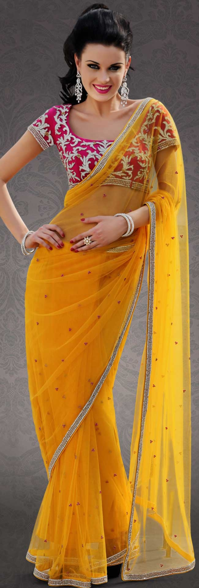 Attract all attentions with this embroidered saree.   This dark yellow net saree is nicely designed with embroidered patch work is done with stone work.   Beautiful embroidery work on saree make attractive to impress all.   This saree gives you a modern and different look in fabulous style.   Contrasting pink blouse is available.   Slight color variations are possible due to differing screen and photograph resolution.