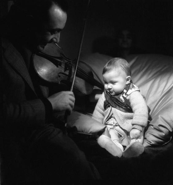 Django Reinhardt joue du violon à son fils Babik, vers 1945. by Emile Savitry