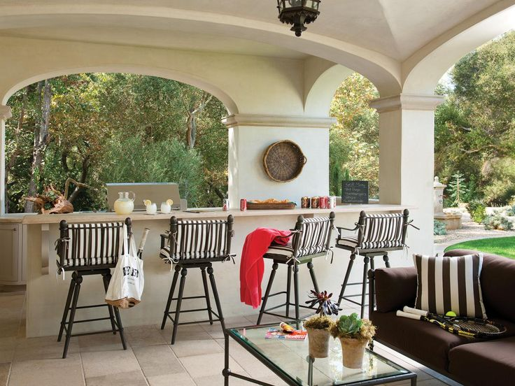 A Mediterranean Loggia Featuring White Arches Offers An Escape From Sunny Days With Outdoor Bar Area And Striped Padded Stools Stone Tiled Floor