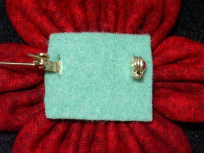 cut 2 little slits in the felt and attach felt and pinback this way for clean look.