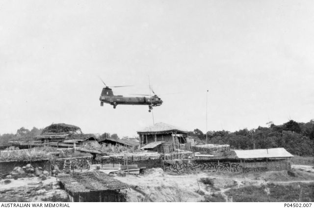 A Belvedere heavy lift transport helicopter from 66 Squadron, RAF, flying low over the sandbagged defences of the forward base camp of A Company, 3rd Battalion, The Royal Australian Regiment (3RAR), at Stass.