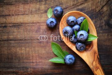 Spoonful of fresh ripe garden blueberries with copy space