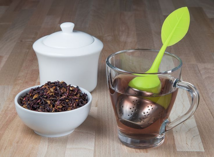 Tea infuser in a cup with loose tea leafs