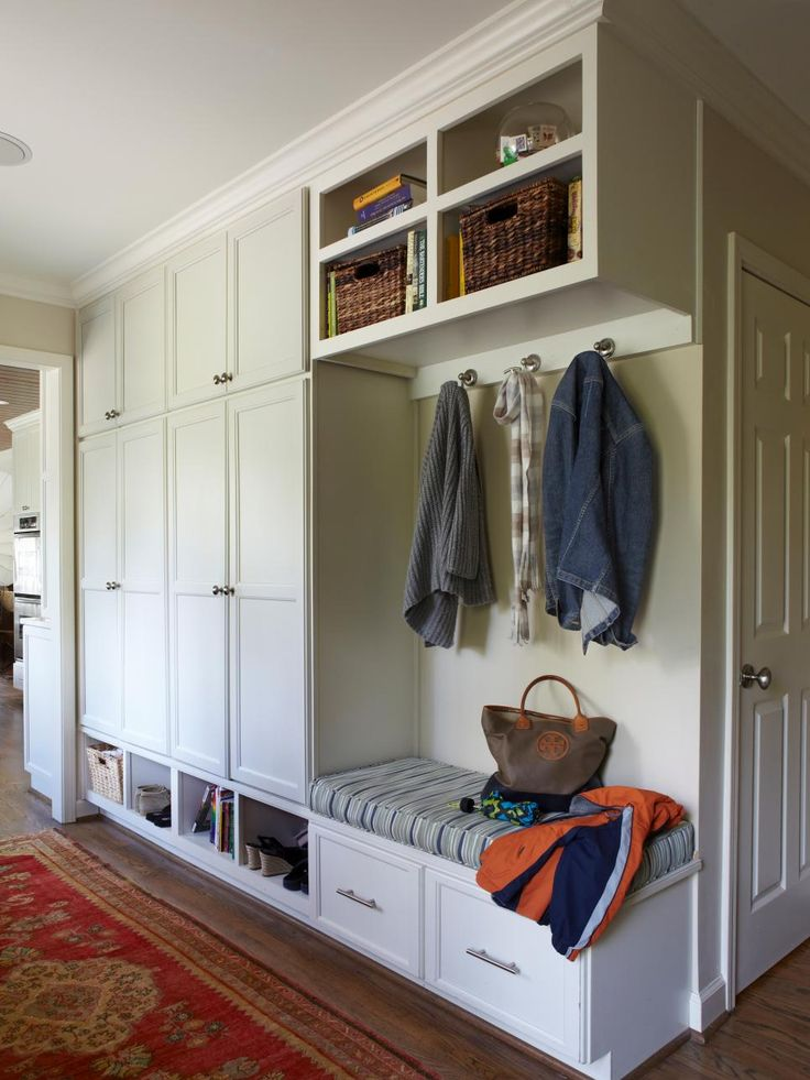 A bench and hooks just inside this home's back door give children a place to drop shoes, jackets and backpacks. Lockers with paneled doors coordinate with the adjacent kitchen and keep clutter out of sight. Cubbies above and drawers below hold seasonal items, while a pretty Oriental runner softens the space.