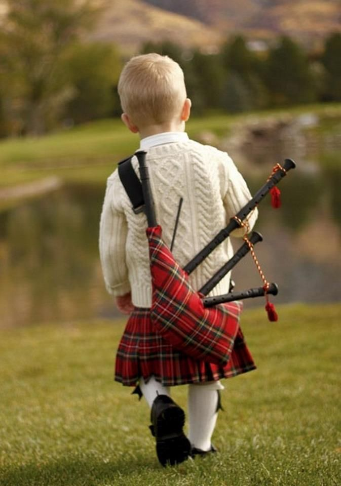 Little boy lugging his bagpipes