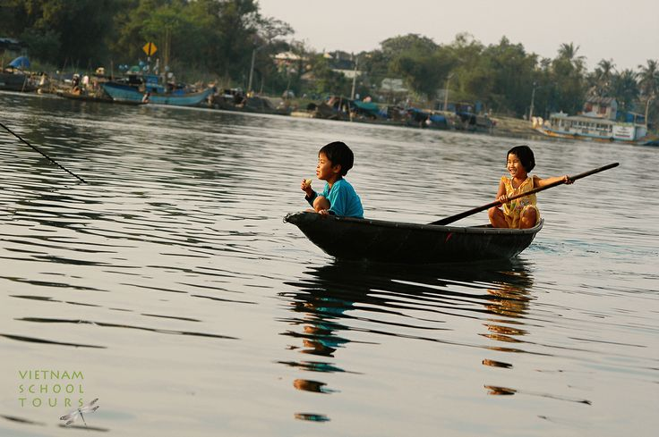 Two kid padling the small boat on Perfume River in Hue