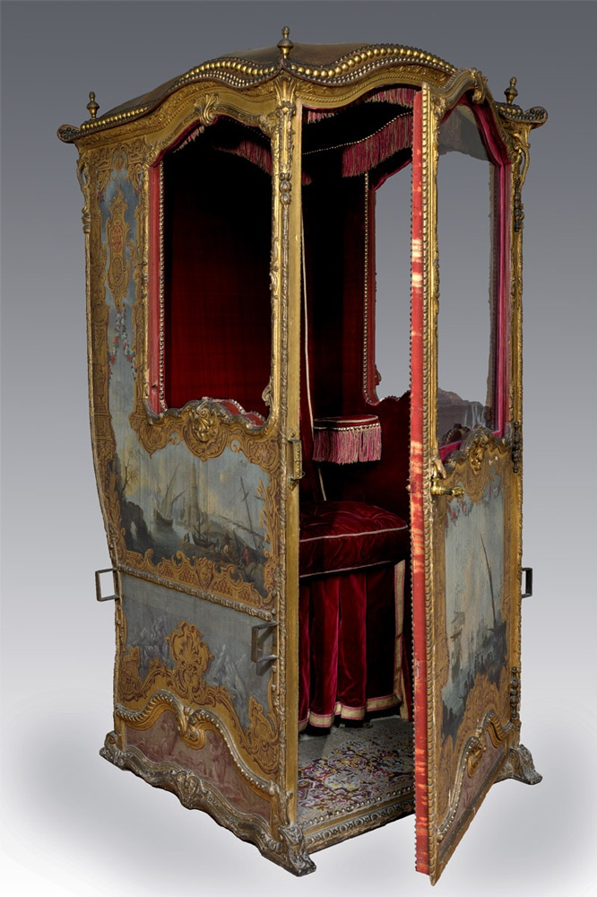 "Seascape sedan chair - 1725-1740. Versailles Arras. This chair, known as the ""Seascape"" chair, which has just been admirably restored, is a wonderful specimen of the forgotten art of carriage production under the Ancien Regime. Dating from the start of the reign of Louis XV, it is completely covered in ships in the style of Adrien Manglard, depicted within a virtuoso frame of trompe-l'oeil gilded paintwork, showing the interlacing letters 'C' and 'L'."