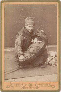 Samisk kvinne ammer spebarn i komse