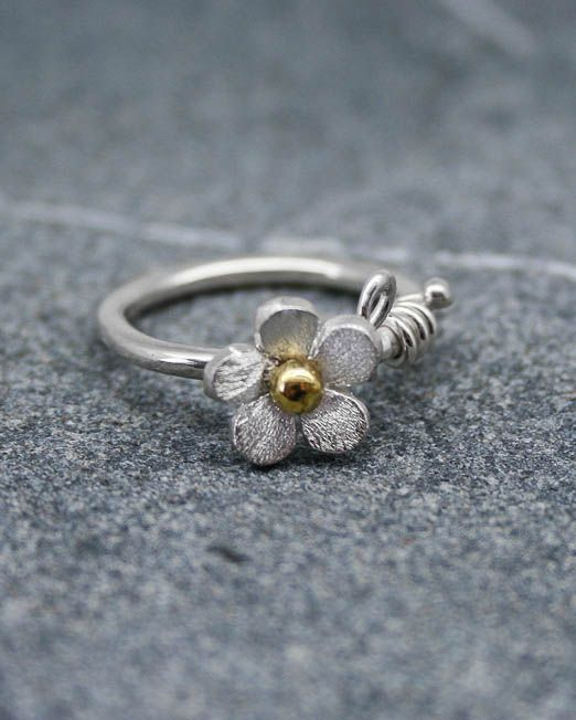 Sweet and simple daisy ring.  This lovely ring is a must for everybody's jewellery box.  Suitable for all occasions.  The daisy has been hand saw pierced then lightly domed with a brass bead to the centre. From the base of the daisy is an applied silver stem wrapping around the band and terminating with small silver bead.  The band is 1.8mm wide. The daisy measures 10mm in diameter.