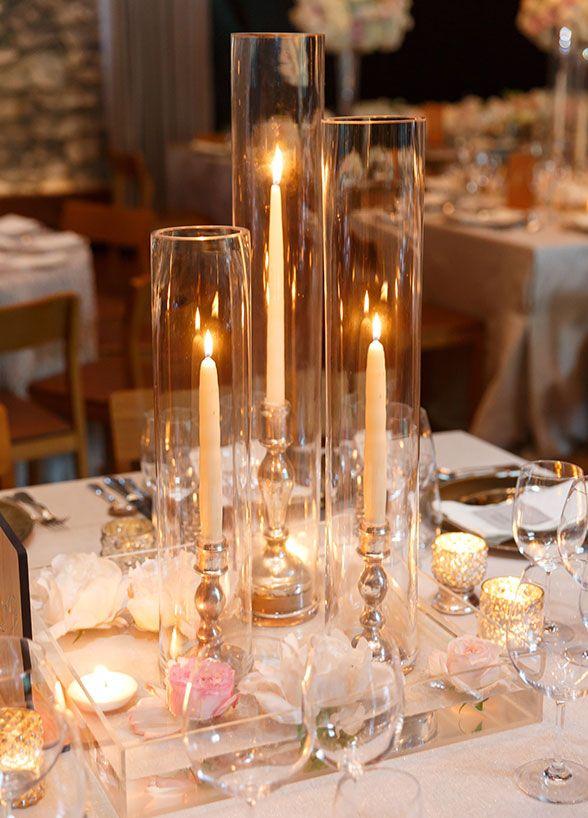 Centros de mesa con jarrones cilíndricos con candelabros y velas largas por dentro. #CentroDeMesa