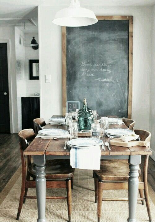 Rustic wooden kitchen table complete with authentic chairs and a feature black board displayed on the wall