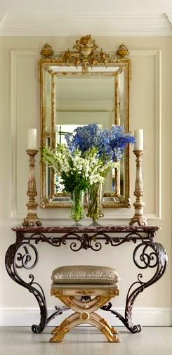 Hallways with height require furnishings which are proportioned to their specifications. A smaller mirror and candle sticks would be lost in a space this size.