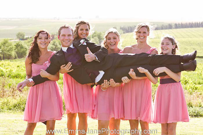 Bridesmaids carry groom