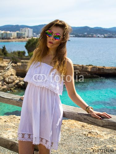 Cute hippie girl standing on a cliff by the sea