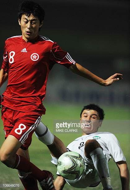 Xu Deshuai of Hong Kong vies with Sherzodbak Karimov of Uzbekistan in their men's group E pool football match at the 16th Asian Games in Guangzhou on...
