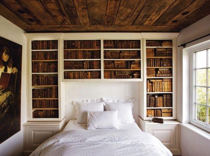 white walls, white bedding, built-in book shelves, wood planks on ceiling, artwork.