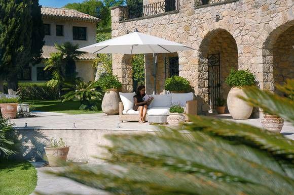 Wie der Außenbereich einer mallorquinischen Finca mutet diese Terrasse an. Große Terrakotta-Töpfe, ein weißer Sonnenschirm und das gemütliche Lounge-Sofa laden zur Siesta ein.